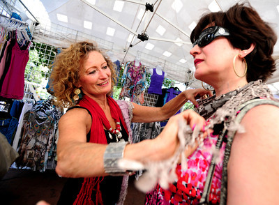 Cheri Nieto, of Boulder helps Diane Janders, of New Jersey try on a scarf at her own business, Cheri's Boutique at the International Festival on Pearl St. Mall Saturday afternoon.  Rachel Woolf/ For the Camera