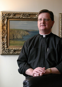 Msgr. Joseph Corbett, Vicar General and Moderator of the Curia, stands before a painting in his office that shows a beach near his hometown Irish village of Stradbally, County Waterford. Archbishop-emeritus John F. Donoghue ordained Msgr. Corbett in Ireland on May 28, 1995. In June of that year he took on his first assignment at All Saints Church, Dunwoody.