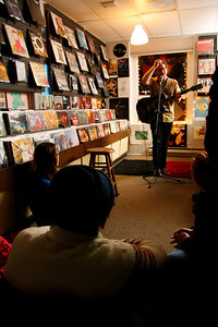 Lansing Community College student Joe McAndrew banters with the crowd in the Record Lounge. McAndrew, who has been playing guitar for about two years, closed the show after Irwin Vega's performance.