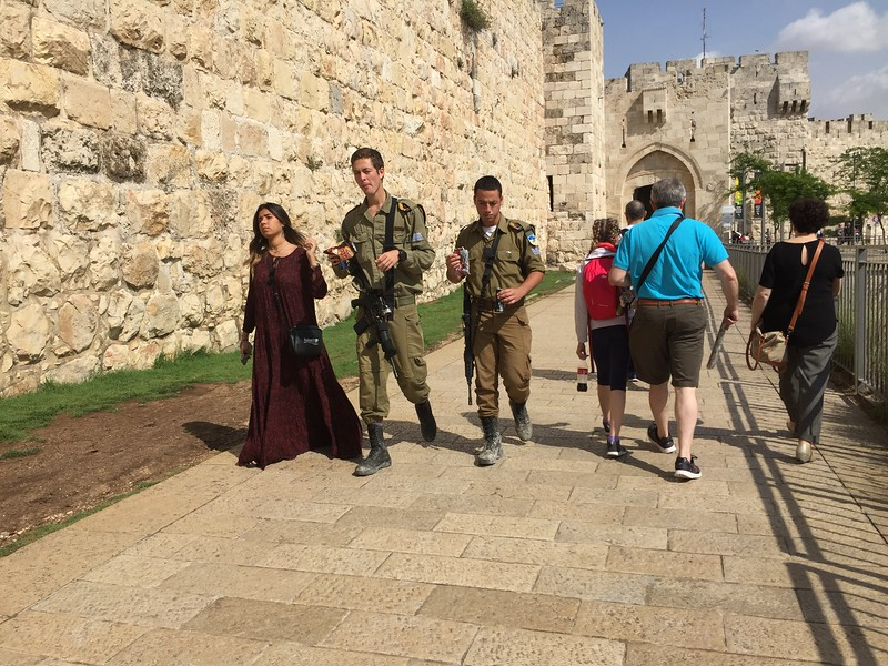 Military soldiers walk side-by-side with tourists and citizens, as they take a snack break just pass Jaffa Gate.  Since it is required that young Israeli adults serve in the military after high school.  It is also common not to see many older soldiers.