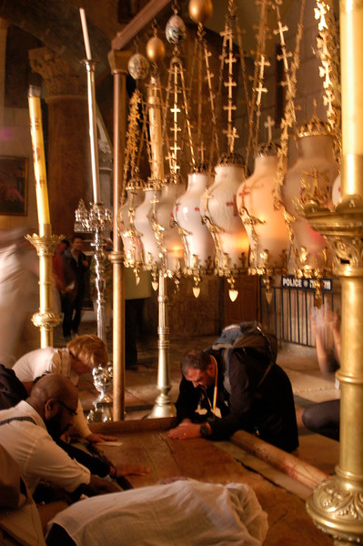 Prayer at the entrance of the church, where the stone of The Anointing is touched by many.  Tradition says that Jesus' body was prepared for burial here.