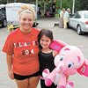 Gina Moore, 7, of Neshannock Township shows off the big pink elephant that her cousin, 18-year-old Alexandria Moore, spent most of the day and a good deal of money winning for her. — Sam Luptak Jr.