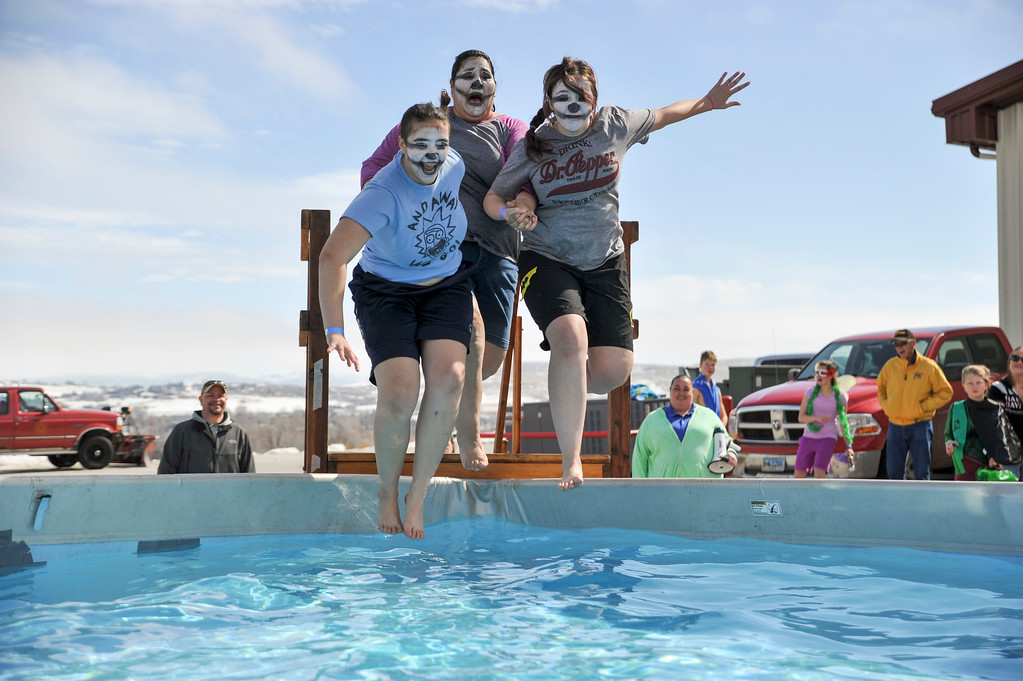 Ashleigh Fox | The Sheridan Press<br /> Representatives for the Masters Special Olympics team jump into the icy waters of the pool for the Jackalope Jump at Goose Valley Fire Department Saturday, March 17, 2018.