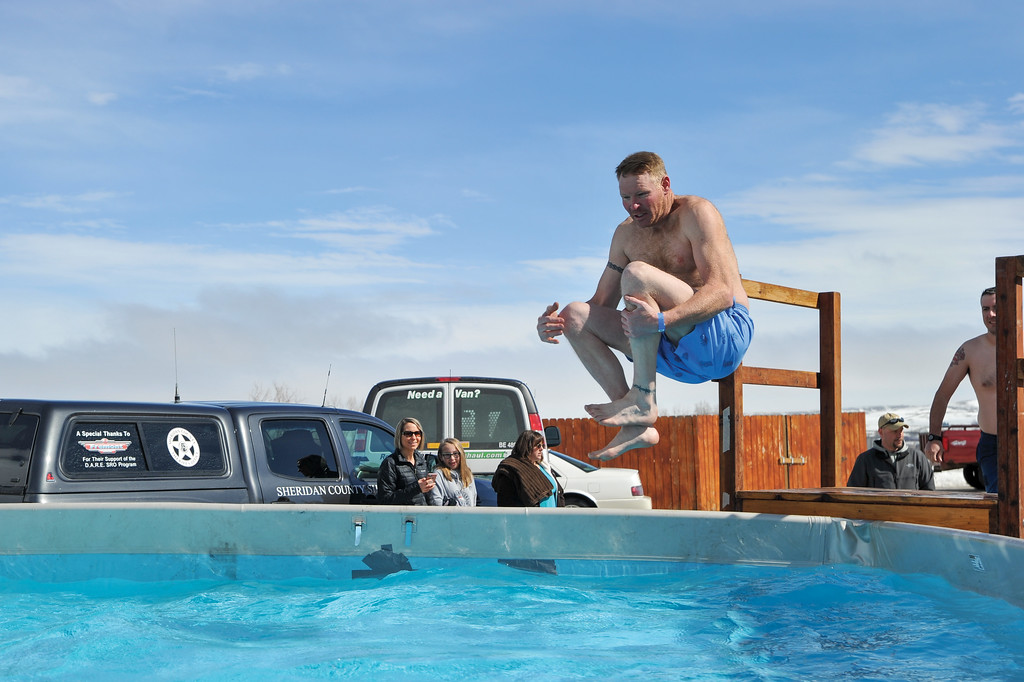 Ashleigh Fox | The Sheridan Press<br /> Goose Valley Fire Department volunteer Justin Johnston cannonballs into the icy waters at the Jackalope Jump Saturday, March 17, 2018. GVFD hosts the event each year.