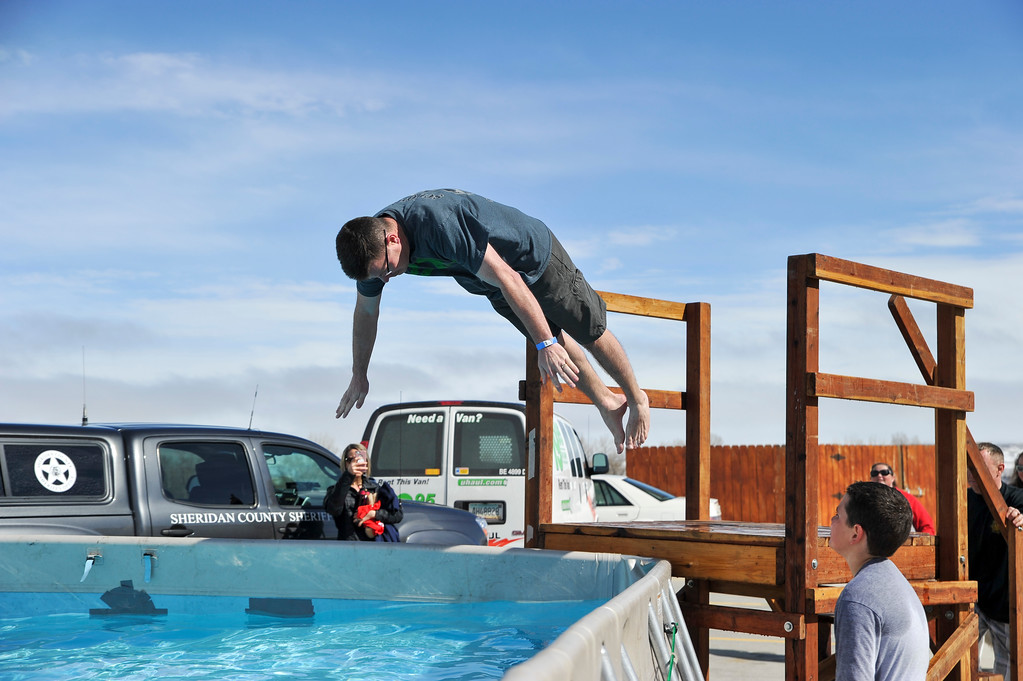 Ashleigh Fox | The Sheridan Press<br /> Wyoming Highway Patrol Captain Jason Green dives into the icy waters at the Jackalope Jump Saturday, March 17, 2018. The jump raises funds for local Special Olympics teams each year.