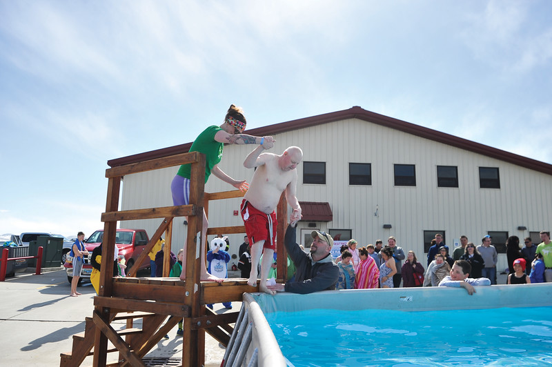 Ashleigh Fox | The Sheridan Press<br /> RENEW community liasion Leita Rolfe helps RENEW member Russell Robb into the pool at the Jackalope Jump Saturday, March 17, 2018. The event raised nearly $8,700 for local Special Olympics teams.