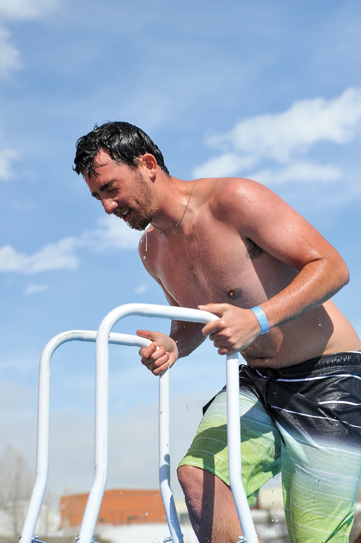 Ashleigh Fox | The Sheridan Press<br /> Ty Fauber, a volunteer with Goose Valley Fire Department, reacts to the cold water after jumping at the Jackalope Jump Saturday, March 17, 2018. GVFD hosts the jump each year.