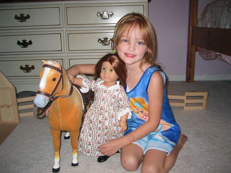 Caroline with her new toys:  American Girl doll Felicity and her palamino horse.