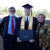 Proud parents stand with the graduate.