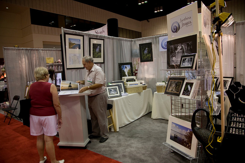 Showing a show attendee our 2009 Lighthouses of Florida calendar in July 2009 as we were presenting the 2010 issue.