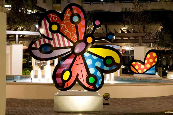 Night time by the fountain area featuring the colorful Britto sculptures.