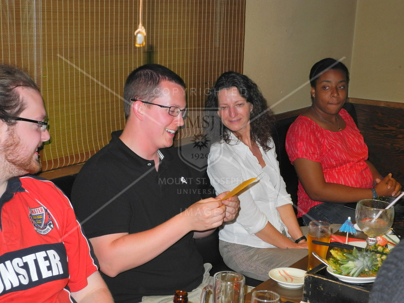 Tokyo, Watami Izakaya Restaurant, on the final evening, the group enjoys an awards ceremony.  Jeff Cox reads his award out loud as Corey Brann, Patty Queener and Briana Reynolds look on.
