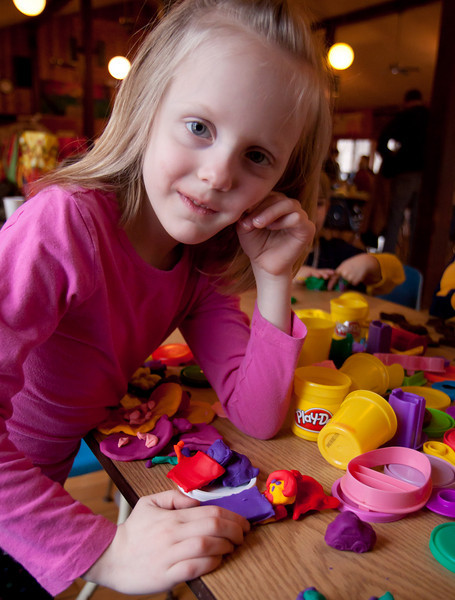 Katie posing over her Play-doh creations.