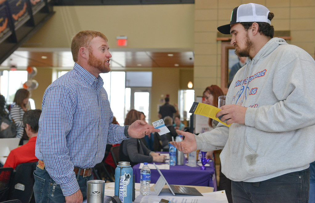 Justin Sheely | The Sheridan Press<br /> Erick Loden of Dave oden Construction offers his business card to welding student Jeremy Rodney during the Spring Career Network Fair at Sheridan College Wednesday, April 11, 2018.