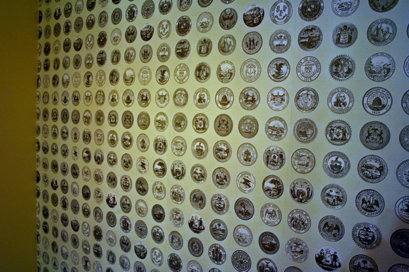 Wallpaper along staircase to the 2d floor contains the seals of the 48 states.