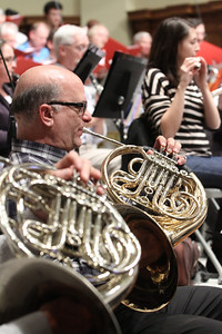 French horn player Jay Hanselman plays in the foreground as flute and piccolo player Judith Gilbert plays in the background.