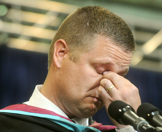 Globe/Roger Nomer<br /> Joplin Superintendent C.J. Huff wipes away a tear as he emotionally addresses the Joplin High School graduating class on Monday.