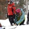 Record-Eagle/Garret Leiva<br /> Charlie Black, 5, of Traverse City, waits to hit the slopes as his mother, Sally Black adjusts his ski bindings during the Jr. Air Affair skills clinic and competition Saturday at Mt. Holiday.