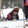 Record-Eagle/Garret Leiva<br /> Fletcher Reyher, 10, of Traverse City, checks over his snowboard before hitting the slopes again at the Jr. Air Affair skills clinic and competition Saturday at Mt. Holiday.
