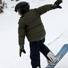 Record-Eagle/Garret Leiva<br /> Sam Huver, 10, of Williamsburg, bends his snowboard as he comes back down to earth at the Jr. Air Affair skills clinic and competition Saturday at Mt. Holiday.