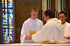 Justin Krenke assists Fr. Jack Kurps at the altar while James Nguyen looks on,