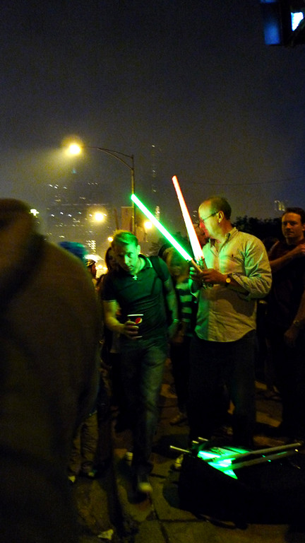 It was amazing seeing the hundreds (thousands?) of people leaving the lakefront.  Here the street vendor was selling light sabers.