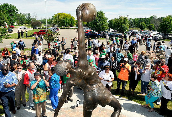 "John P. Cleary | The Herald Bulletin<br /> People come up to get a close-up look at the Jumpin' Johnny Wilson sculpture titled ""Far Reaching Goals"" that was unveiled Friday in front of the Anderson High School entrance."