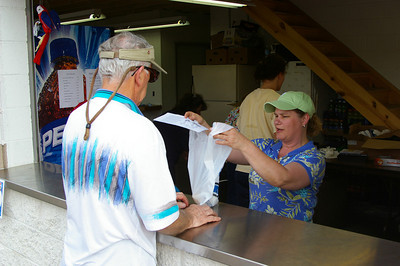 IMGP1167: Friday, June 1st, 2007: Sandy Hess, Islandfest Committee Chair, shows info on the upcoming August Islandfest event as she delivers a barbecue chicken dinner to customer.