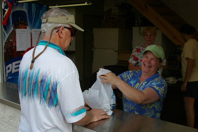 IMGP1169: Friday, June 1st, 2007: Sandy Hess, Islandfest Committee Chair, happily serves a barbecue chicken dinner to customer.