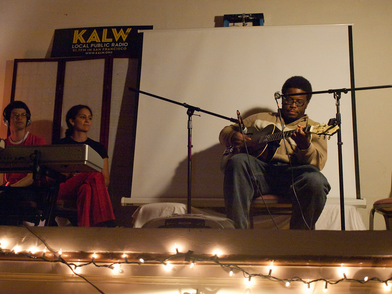 Quinn Deveaux on guitar, with Seth Samuel and Martina Castro of the production team. Crosscurrents Live, KALW Mission Arts and Performance Project, MAPP, December 2011. The Polish Club, 3040-22nd St., Mission district, San Francisco, California.