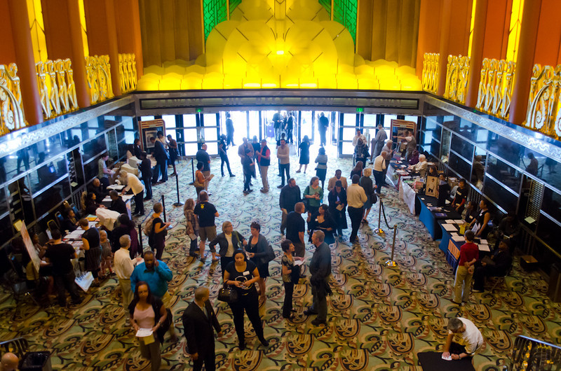 Lobby and entrance with tables. KALW Presents Tavis Smiley & Cornel West, Paramount Theatre, 2025 Broadway, Oakland, California.