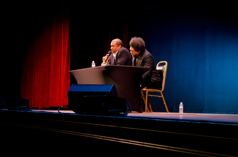 Tavis Smiley and Cornel West at table on stage. KALW Presents Tavis Smiley & Cornel West, Paramount Theatre, 2025 Broadway, Oakland, California.