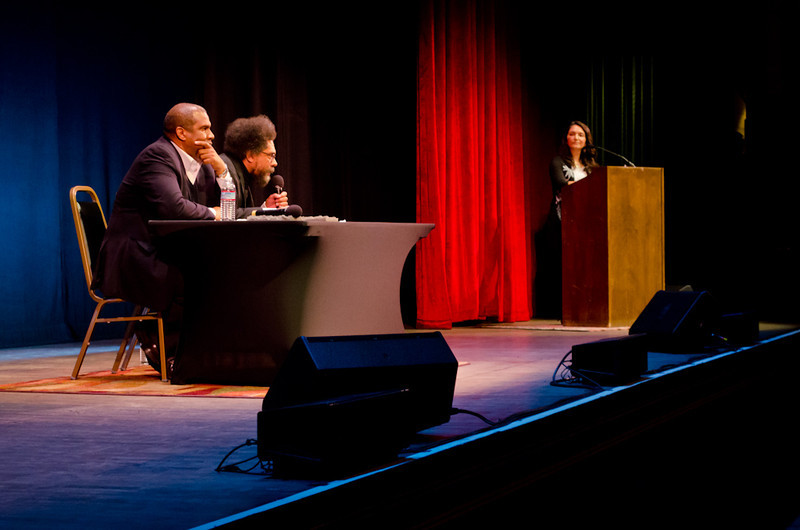 Tavis Smiley and Cornel West at table, with Rose Aguilar at podium. KALW Presents Tavis Smiley & Cornel West, Paramount Theatre, 2025 Broadway, Oakland, California.