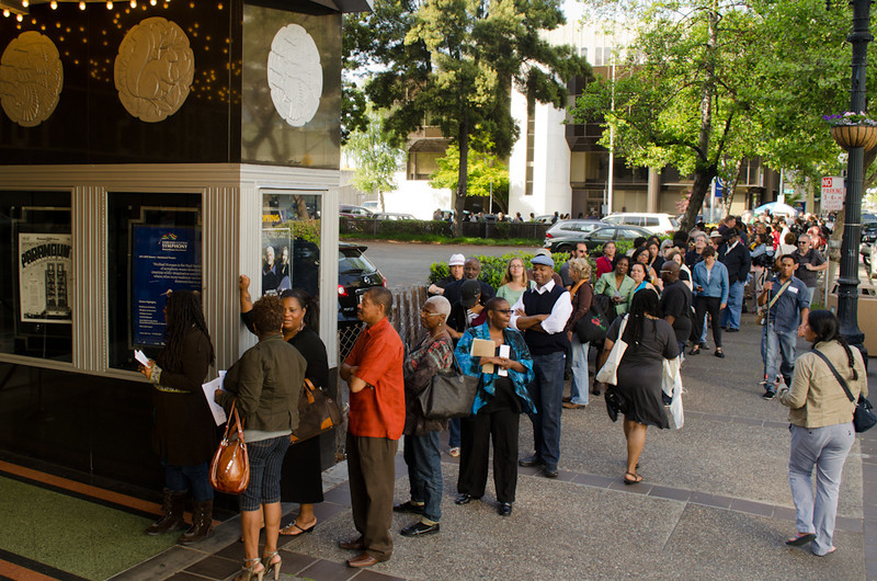 Outside queue along sidewalk. KALW Presents Tavis Smiley & Cornel West, Paramount Theatre, 2025 Broadway, Oakland, California.