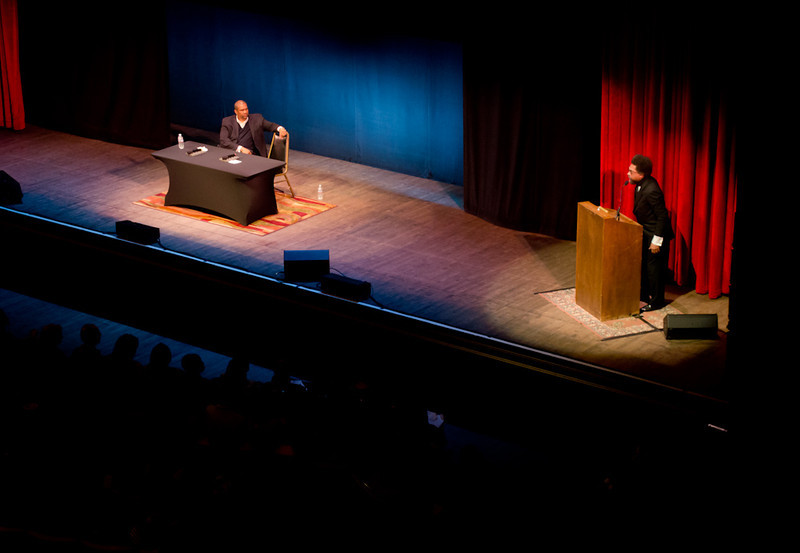 Cornel West at podium and Tavis Smiley at table. KALW Presents Tavis Smiley & Cornel West, Paramount Theatre, 2025 Broadway, Oakland, California.