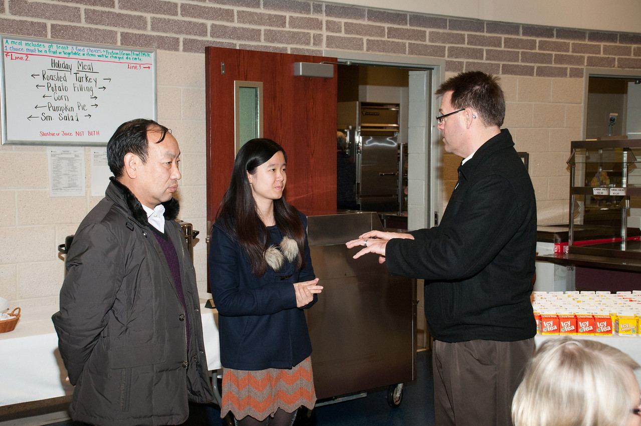 Patriot photos by Scott Weldon Carl Weston chats with Principal Wang while Li Ziyan, a KU student, interprets during the KASD Thanksgiving Community Potluck Dinner on Nov. 21.