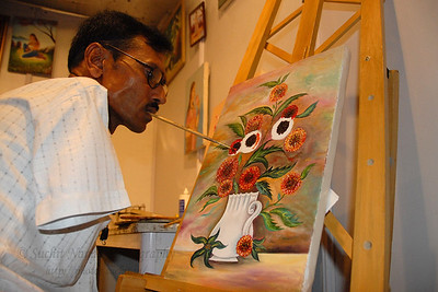 Artists Without Hands at work. Manji L. Ramani painting with his mouth as he does not have hands.  Special skilled artist live at the Kala Ghoda Arts Festival, Feb 2007  A member of MFPA (Indian Mouth & Food Painting Artists).