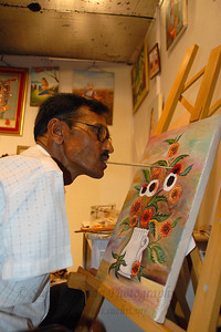 Artists Without Hands at work. Manji L. Ramani who does not have hands painting with his mouth.  Special skilled artist live at the Kala Ghoda Arts Festival, Feb 2007.  Member of MFPA (Indian Mouth & Food Painting Artists).
