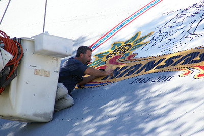 "Kenny Unrein finishing painting the last letter ""K"" on the logo"