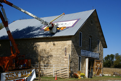 Kenny Unrein painting a sunflower logo on the Stone Barn Mercantile