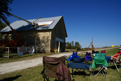 Kenny Unrein painting a sunflower logo on the Stone Barn Mercantile. Setting up chairs to watch.