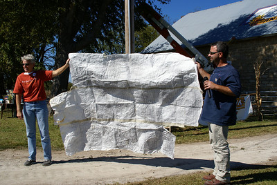 Kenny Unrein and Marci Penner displaying Kenny's template used for painging the logo.