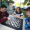 Opening ceremony and concert kicking off a more active Kerouac Park. Armando Ortis, 17, left, and Kevin Snow, 17, right, play chess as Snow's sister Cat Snow, 15, watches. All are of Lowell. (SUN/Julia Malakie)