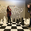 Khmer New Year's celebration at UMass Lowell's University Crossing. From left, Lowell High students Miracle Ojinka, 16, Annari Phomsouvandara, 17, and Saomenea Phorn, 16, who were volunteering at Khmer New Year, play with the giant chess set at University Crossing. It was Annari's first time playing chess, and Miracle was helping both players. (SUN/Julia Malakie)