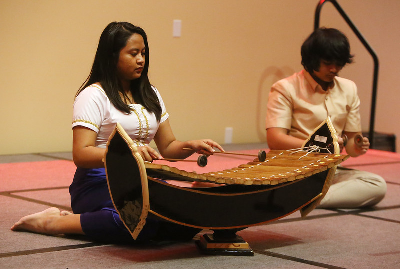Khmer New Year's celebration at UMass Lowell's University Crossing. Christina Prum, 17, plays the roneat. At right is Vincent Var, 14. Both are from Lowell. (SUN/Julia Malakie)