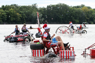 3rd annual Kinetic Sculpture Race entries exit the Merrimack River at Rynne Beach. From left, Kerouac Attack Pack, Where's Waldo?, and The Lottery. (SUN/Julia Malakie)