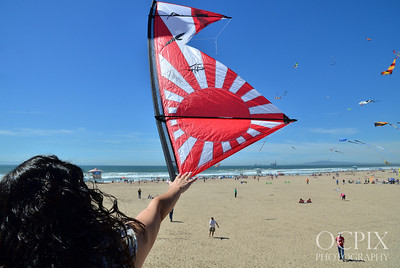 Wide shot of woman reaching out to touch kite