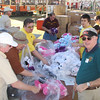 Phoenix Kiwanis Club members and OakCraft employees work feverishly preparing bags of stuff animals for all of the children attending the event.