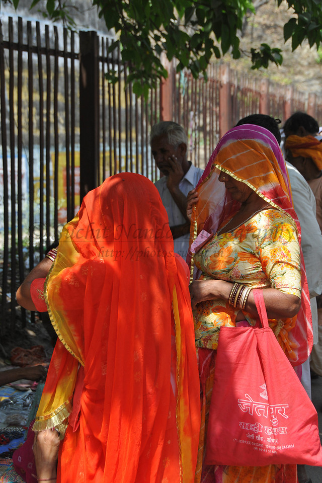 Women in bright coloured sarees at Haridwar.<br /> <br /> Kumbh Mela is the biggest religious gatherings on the planet which takes places on the banks of the river Ganga. The number of pilgrims this year is expected to exceed around five million since the first day Jan 14 till the time it concludes on April 28, 2010. Haridwar, Uttarakhand. North India.