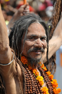 Naga sadhus dance and perform aerobic moves as they head to Har Ki Pauri for the holy dip. As per tradition they have the first right of bathing in the holy Ganga on the occasion of Shahi Snan in Kumbh Mela.  Kumbh Mela is the biggest religious gatherings on the planet which takes places on the banks of the river Ganga. The number of pilgrims this year is expected to exceed around five million since the first day Jan 14 till the time it concludes on April 28, 2010. The auspicious days of the shahi snan or royal baths usually draw hundreds of thousands of devotees to the Har Ki Paudi and other banks of the river. Uttarakhand. North India. The occasion draws pilgrims from around the world and severly overloads the infrastructure so most of the city is shut down for any vehicles other than security or emergency services so a sea of humanity walks through the city to get to the bathing ghats.